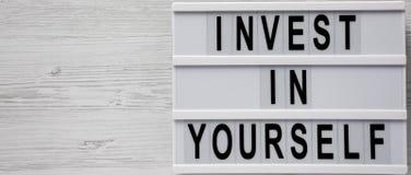 'Invierta en sí mismo 'las palabras en un tablero moderno sobre el fondo de madera blanco, visión superior Endecha de arriba, pla foto de archivo