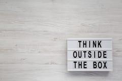 'Piense fuera de las palabras de la caja en un tablero moderno en una superficie de madera blanca, visión superior Endecha plana, fotografía de archivo