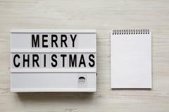 'Die Wörter der frohen Weihnachten auf lightbox, leerer Notizblock über weißem hölzernem Hintergrund, obenliegende Ansicht Flache stockfotos