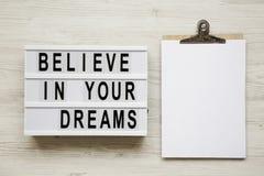 'Geloof in het woord van uw dromen op moderne raad, noticeboard over witte houten achtergrond, hoogste mening Vlak leg hierboven, stock afbeeldingen
