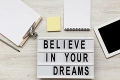 'Geloof in het woord van uw dromen op moderne raad, noticeboard, potlood en tablet over witte houten achtergrond, luchtmening Bov stock foto's