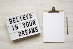 'Geloof in het woord van uw dromen op moderne raad, noticeboard, potlood over witte houten oppervlakte, luchtmening De hoogste vl stock foto's