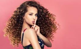 'Houd geheim ', jong, houdt de mooie vrouw vinger voor haar lippen stock afbeeldingen