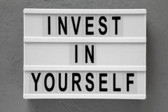 ?Investeer in zich ?woorden op een lightbox over grijze achtergrond, hoogste mening Lucht, vlak leg hierboven, van Close-up royalty-vrije stock afbeelding