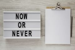 'Jetzt oder nie 'Wort auf lightbox, Klemmbrett mit Blatt Papier auf einer weißen Holzoberfläche, Draufsicht Raum für Text stockbilder
