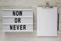 'Jetzt oder nie 'Wort auf lightbox, Klemmbrett mit Blatt Papier auf einer weißen Holzoberfläche, Draufsicht Raum für Text lizenzfreie stockbilder