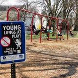 'Jonge Longen bij Spel 'teken op speelplaats stock foto's