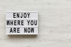 """""""Απολαύστε όπου είστε τώρα """"λέξεις στο σύγχρονο πίνακα πέρα από το άσπρο ξύλινο υπόβαθρο, υπερυψωμένο διάστημα αντιγράφων στοκ εικόνα με δικαίωμα ελεύθερης χρήσης"""
