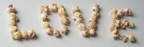 """""""amour """"écrit avec le maïs éclaté rose blanc photographie stock libre de droits"""