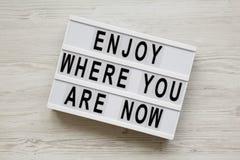 """""""Appréciez où vous êtes maintenant """"des mots sur le conseil moderne au-dessus de la surface en bois blanche, vue aérienne Configu images libres de droits"""