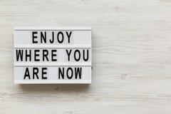 """""""Appréciez où vous êtes maintenant """"des mots sur le conseil moderne au-dessus du fond en bois blanc, au-dessus Copiez l'espace image libre de droits"""