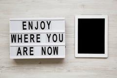 """""""Appréciez où vous êtes maintenant """"des mots sur le lightbox, comprimé avec l'écran vide au-dessus du fond en bois blanc, vue aér images libres de droits"""