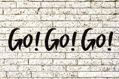"""""""Go! Go! Go!"""" motivational text written on a white stone brick wall background vector illustration"""