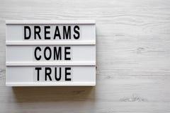 """""""I sogni si avverano """"le parole sul bordo moderno sopra superficie di legno bianca, vista sopraelevata Vista superiore, da sopra immagini stock libere da diritti"""