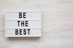 """""""Soyez les meilleurs """"mots sur un conseil moderne sur un fond en bois blanc Configuration plate, vue a?rienne et sup?rieure Copie photos stock"""