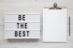 """""""Soyez les meilleurs """"mots sur un lightbox, presse-papiers avec la page du papier blanche sur un fond en bois blanc La configurat photographie stock libre de droits"""