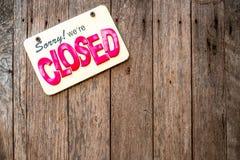 """""""К сожалению мы закрытый """"знак с желтой предпосылкой и красные и черные английские тексты прикрепленные в деревянную дверь стоковое фото"""