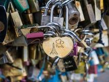 """""""Parijs"""" op liefdeslot wordt gegraveerd in close-up van liefdesloten op de brug die van Parijs Stock Afbeeldingen"""