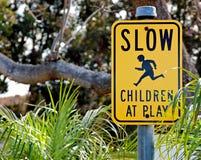 Rallenti… i bambini al segnale stradale del gioco Fotografia Stock