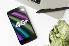 ‹Mobile d'†de ‹de l'†4g + sur l'écran, dans l'espace de travail propre Images stock
