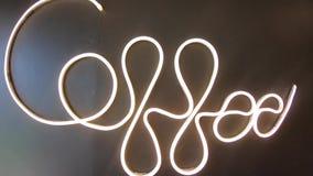 """€œWords del """"Coffee de las imágenes de vídeo escritos con las luces de neón en un fondo negro de la pared metrajes"""