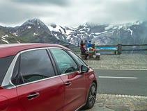 """€ delle alpi, Austria """"27 luglio 2017:: Famiglia che riposa nelle alpi Austria L'automobile rossa per il viaggio sta stando vici Fotografie Stock Libere da Diritti"""