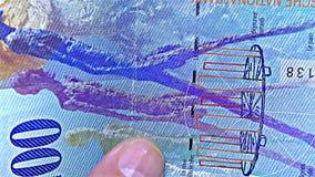 """€ suizo del dinero """"100 CHF, francos del centavo - raya olográfica de la raya del †iridiscente del billete de banco """", detalle almacen de metraje de vídeo"""