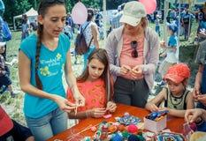 """€""""volontär för ung kvinna som förklarar hur man sticker den färgrika tabellservetten Royaltyfri Foto"""