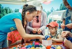 """€""""volontär för ung kvinna som förklarar hur man sticker den färgrika tabellservetten Arkivfoto"""