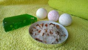 浴、一块大软肥皂和腌制槽用食盐的三颗逗人喜爱的小的炸弹与在黄色毛巾的花瓣 库存图片