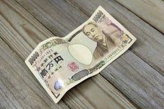 一万在木背景的日元钞票 免版税库存照片