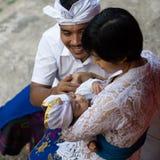 一个一个月的巴厘语男婴的画象有他的母亲和父亲的 他们穿传统巴厘语衣裳 婴孩跌倒 免版税库存照片