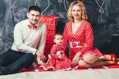 一个一岁的女孩在她的在一件红色礼服的生日在与她的父母的一个白色圈子在单独一个大图附近坐 库存照片