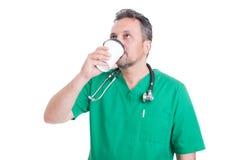从一个一次性杯子的医生饮用的咖啡 免版税库存图片