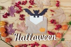 一个万圣夜木桌面的顶视图有纸、信封、棒、莓果和槭树叶子的 复制空间 库存照片