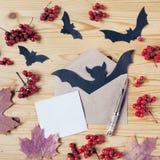 一个万圣夜木桌面的顶视图有纸、笔、信封、棒、莓果和槭树叶子的 复制空间 图库摄影