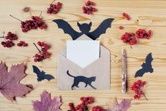 一个万圣夜木桌面的顶视图有纸、笔、猫、信封、棒、莓果和槭树叶子的 复制空间 库存图片