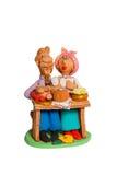 一个丈夫和妻子的小雕象在桌上用食物 免版税库存图片