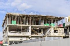 一个三层房子建设中反对天空的一个块 免版税库存图片