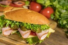 一个三明治用乳酪、火腿、莴苣、蕃茄和酱瓜在一张木桌上说谎 免版税库存图片