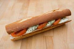 一个三明治用无盐干酪和蕃茄在一个木板 免版税库存图片