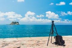 一个三脚架和一个背包在海的背景 库存图片
