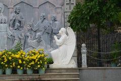 一个下跪天使的雕塑在墙壁的有在圣经的题材的剧情的 免版税库存图片