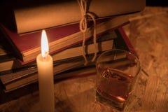 一个不可思议的球、纸卷、一个蜡烛、一杯科涅克白兰地和在夜的黑暗的旧书 库存图片