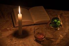 一个不可思议的球、纸卷、一个蜡烛、一杯科涅克白兰地和在夜的黑暗的旧书 免版税库存照片