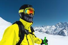 一个与一张闭合的面孔的滑雪者和盔甲的特写镜头画象面具的反对积雪覆盖的山背景和 库存照片