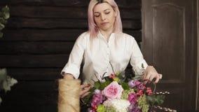一个专业卖花人在她的手上拉紧花束的大词根与麻线串的,拿着花束 股票录像