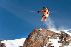 一个专业滑雪者由高峭壁做跃迁下落反对把雪粉末留在的足迹蓝天在 免版税库存照片