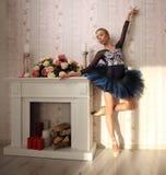 一个专业跳芭蕾舞者的画象在太阳光的在家庭内部,站立在一条腿 芭蕾概念 图库摄影