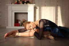 一个专业跳芭蕾舞者的画象坐在太阳光的木地板与闭合的眼睛 有女性的芭蕾舞女演员休息 库存图片
